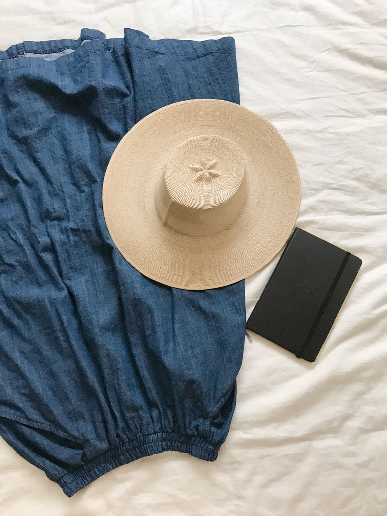Blue denim maxi skirt laid flat on white background with beige hat and black journal.