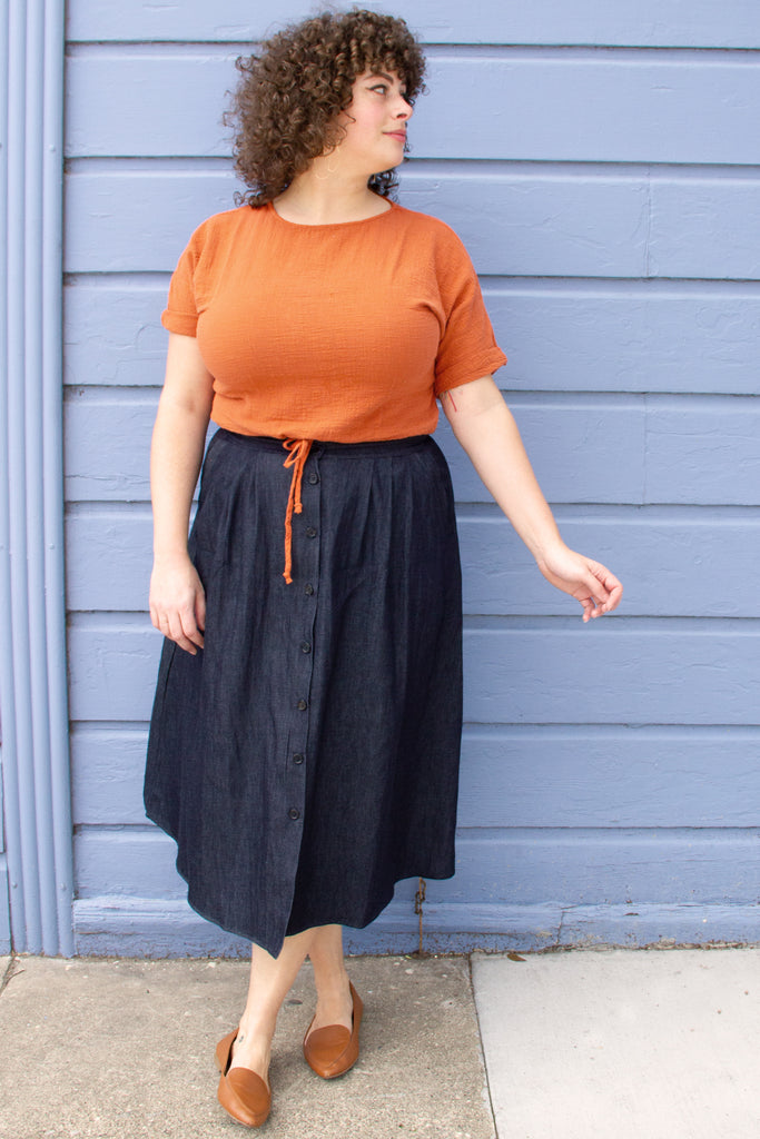 Dark blue denim button up maxi skirt on standing model, paired with orange short sleeve top