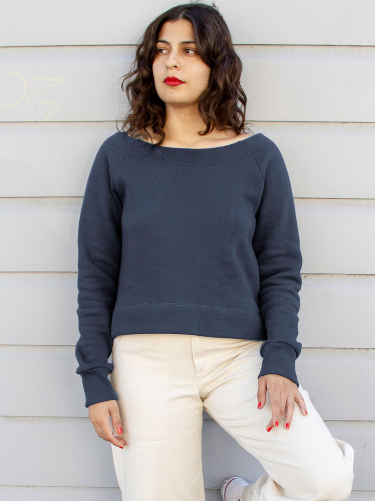 navy blue boat neck sweatshirt on model with white pants