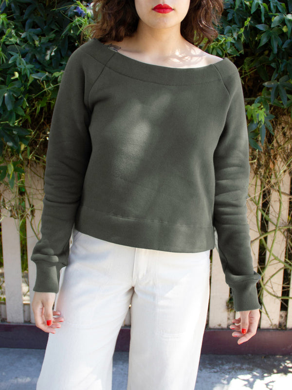 close up of green boatneck sweatshirt on model
