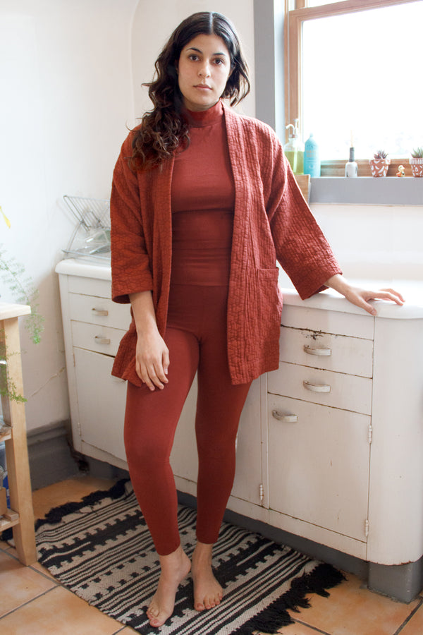 Burnt red high waisted leggings on standing model, paired with burnt red top and cardigan