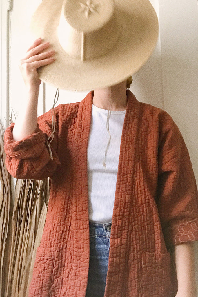 model in quilted rust colored jacket and straw hat