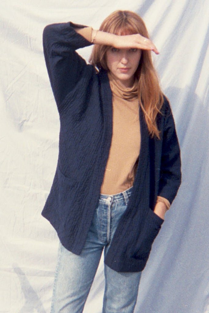 Standing model in navy blue quilted jacket, beige turtleneck, and jeans