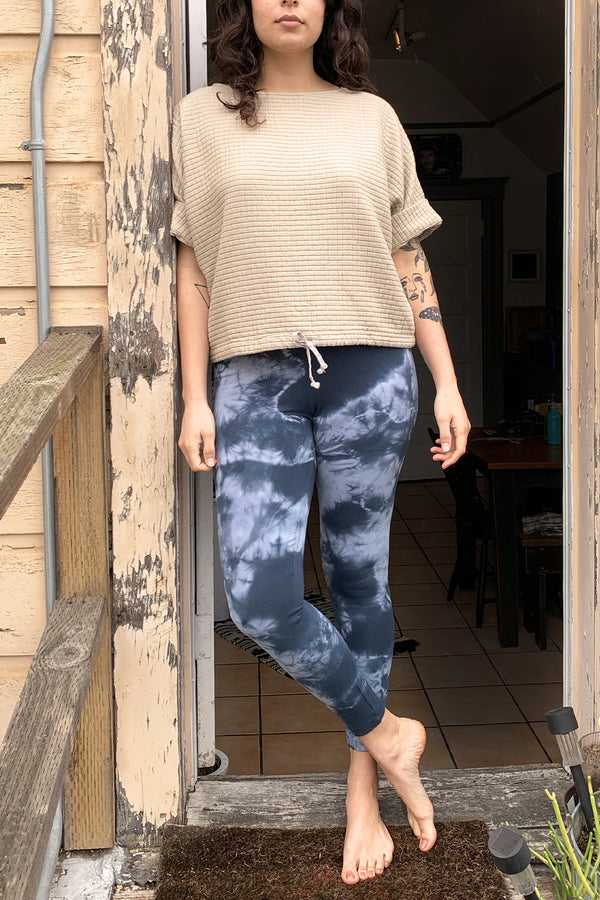 Light and dark blue tie dye high waisted leggings on model paired with cream coloured short sleeve top