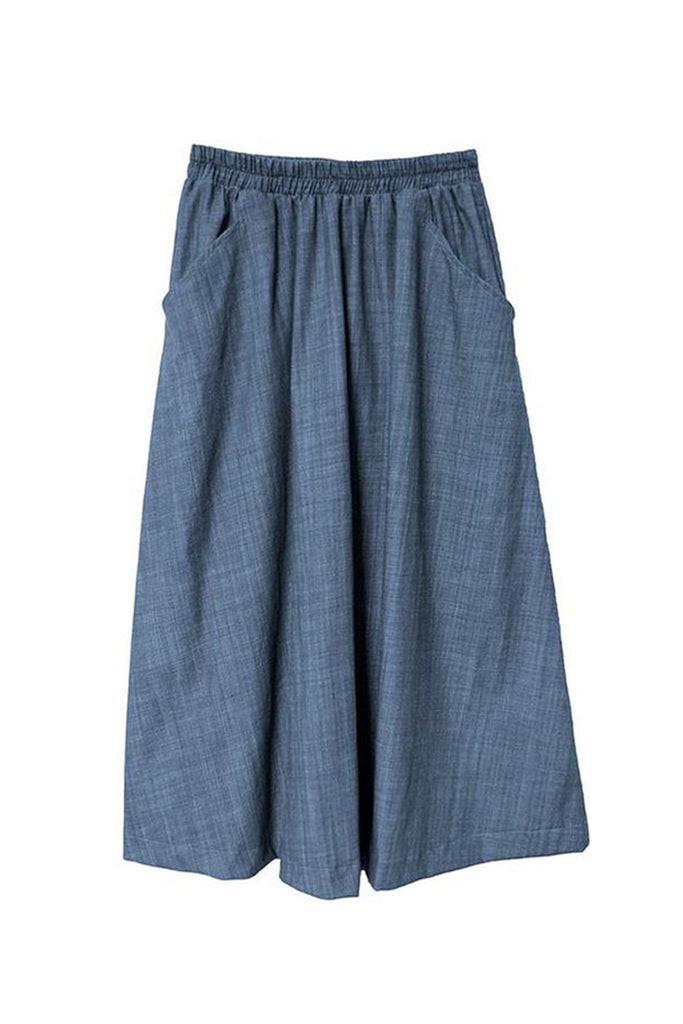 Blue denim maxi skirt with elastic band waist and front pockets against white background