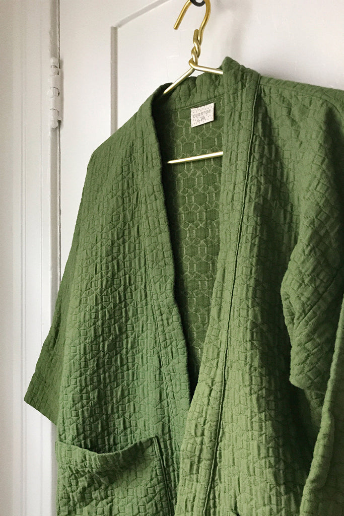 Close up photo of green quilted jacket on hanger