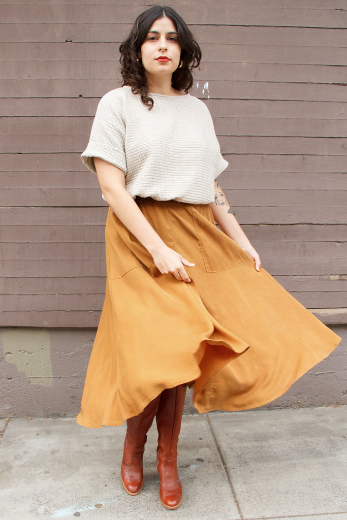 Flowing yellow maxi skirt on standing model, paired with white short sleeve top and brown boots