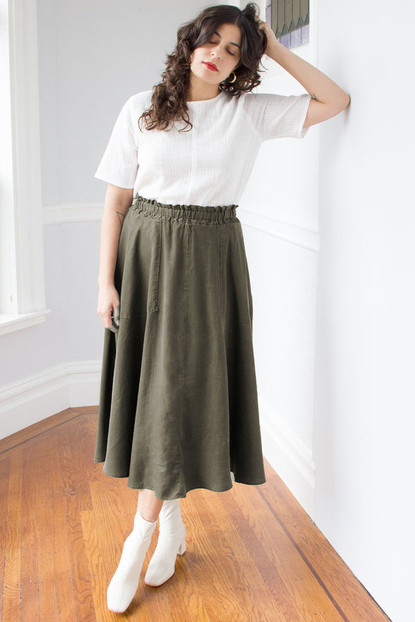 Standing model with hands in hair in army green elastic waist maxi skirt, paired with white short sleeve top and white boots