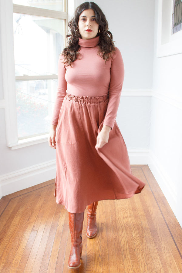 Flowing pink skirt with elastic waist on standing model, paired with pink turtle neck