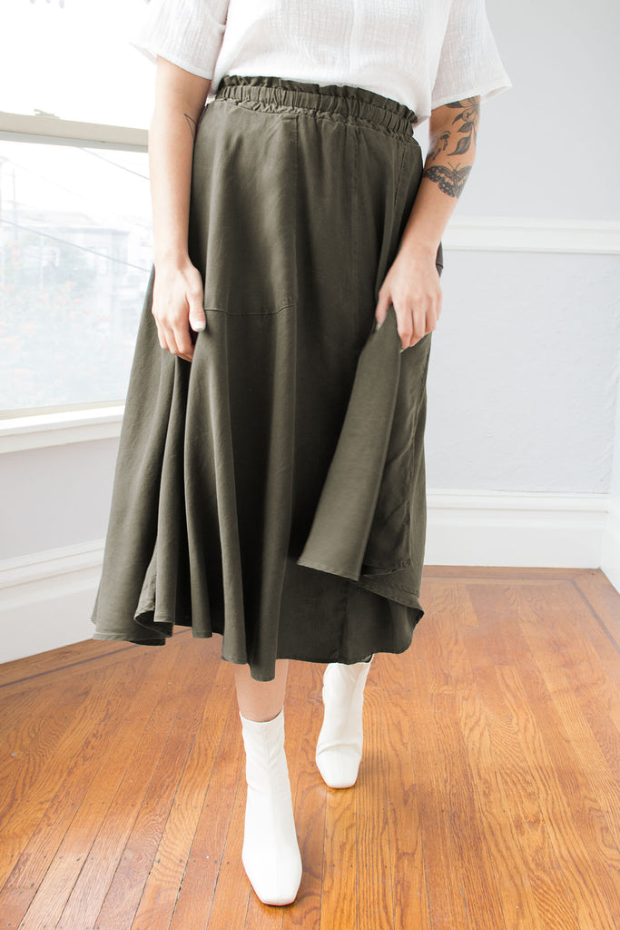 Standing model with hands on mud green maxi skirt, paired with white short sleeve top and white boots