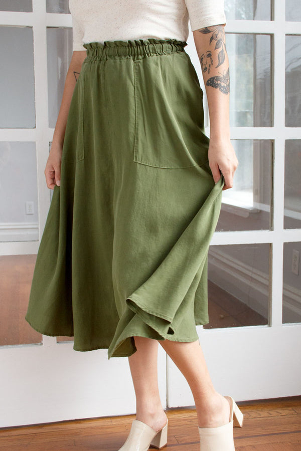 Standing model with hands on flowing green maxi skirt, paired with white short sleeve top and white mule shoes