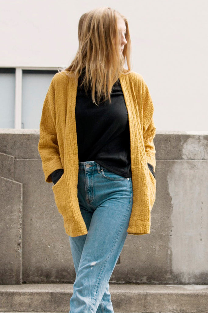 model in black turtleneck and yellow textured jacket with pockets