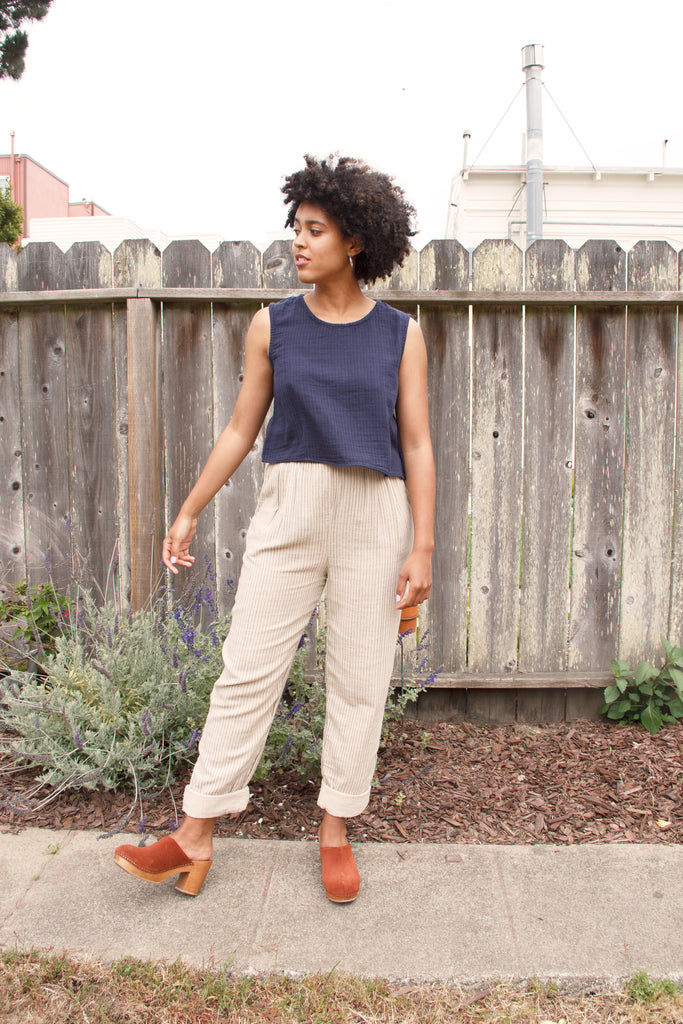 model in pinstripe navy tank top and beige casual pants