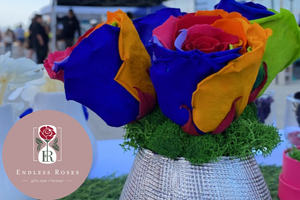 Rainbow roses arrangement in a silver mesh vase, with a background on blurred individuals in a market. Logo on the bottom left of the arrangement.