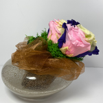 Side profile. 4 extra large prile preserved roses (light green, dark purple, pink mixture) nestled on green preserved moss displayed on pearl shaped copper glass vase