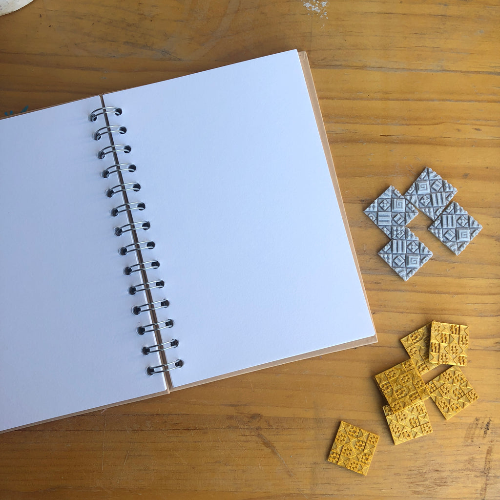 A blank notebook with square 3D texture stickers from Styklet on a wood background.