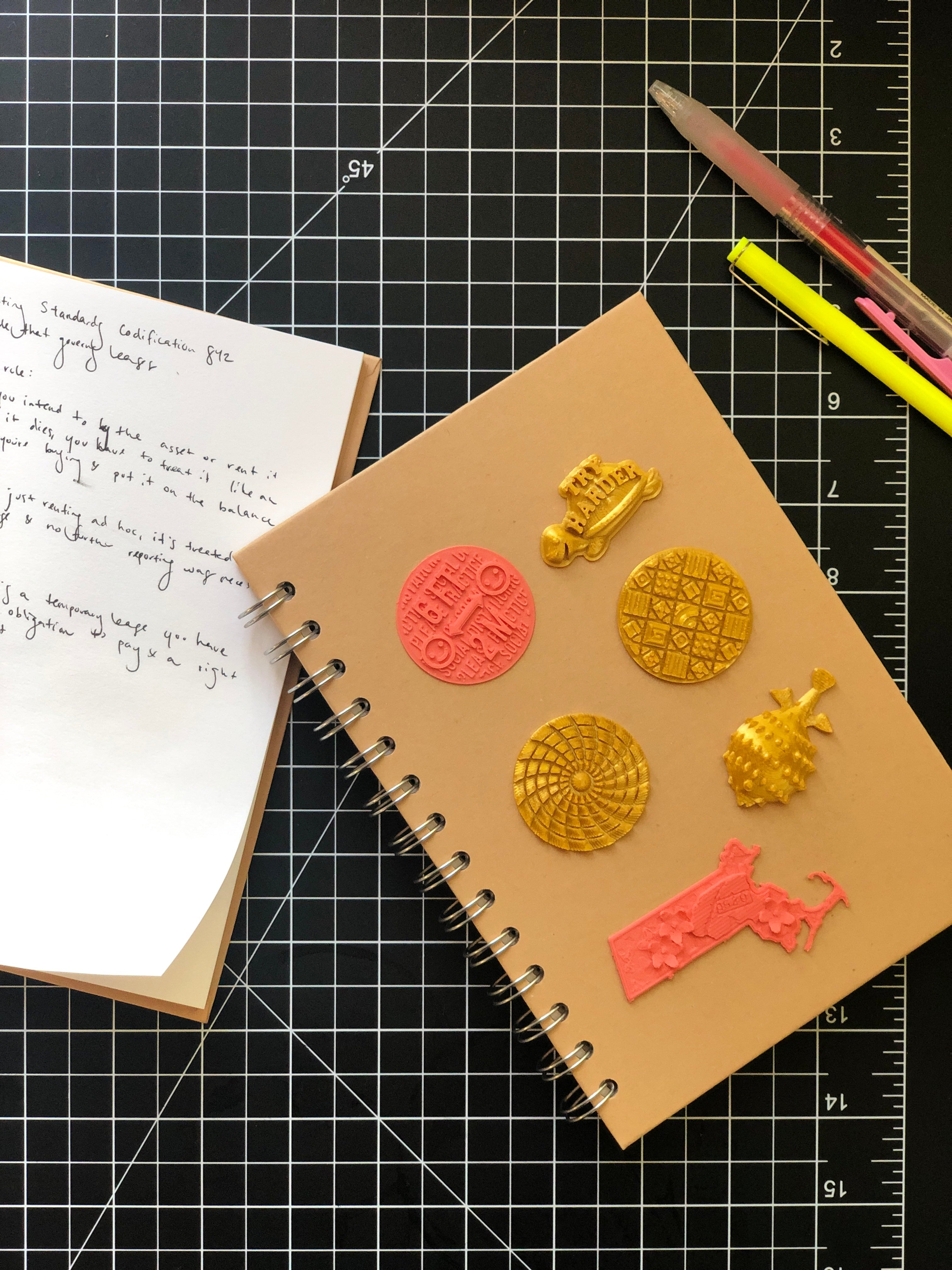 A notebook with various 3D  stickers from Styklet, on a black cutting mat with pens.