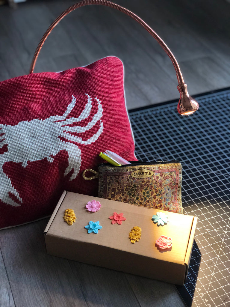 Flower shaped 3D stickers from Styklet on a cardboard box, with a red crab pillow.