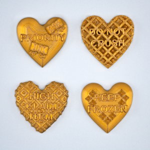 Candy heart stickers from Styklet with the text Do Not Crush, Keep Frozen, Priority, and High Claim Item in gold.