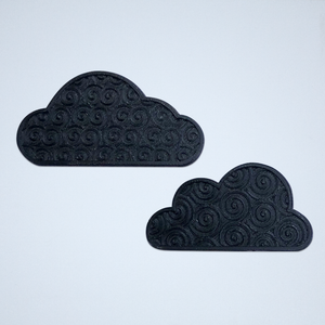A pair of cloud stickers with a 3D spiral texture, 3D printed in black.