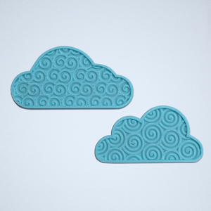 A pair of cloud stickers with a 3D spiral texture, 3D printed in turquoise blue.