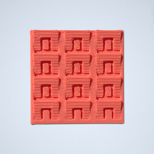 A geometric scale sticker, 3D printed by Styklet in coral.