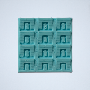 A geometric scale sticker, 3D printed by Styklet in turquoise.