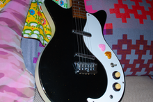 Load image into Gallery viewer, Two candy heart stickers from Styklet, one gold and one pink, decorating a black and white guitar.
