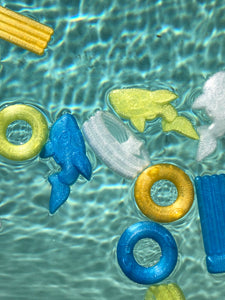 3D stickers of pool floaties, including two whale floatie 3D stickers, floating in a pool.