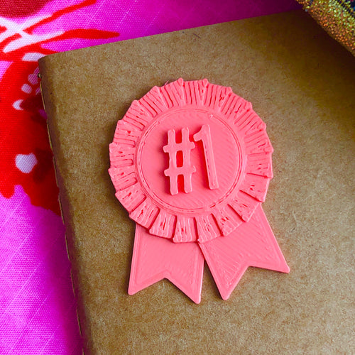 A number 1 ribbon 3D sticker on coral on a kraft paper notebook, with a pink background.
