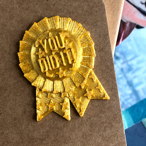 A gold You Did It! Ribbon 3D sticker from Styklet, on a paper notebook.