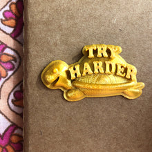"Load image into Gallery viewer, A sticker of a gold turtle that says ""Try Harder"" on a paper notebook."