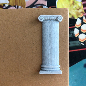 A grey Ionic column sticker on a paper notebook, with a colorful collage in the background.