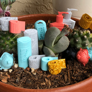 Styklet's new normal collection photographed in a cactus garden, with disinfectant wipes in turquoise and gray.