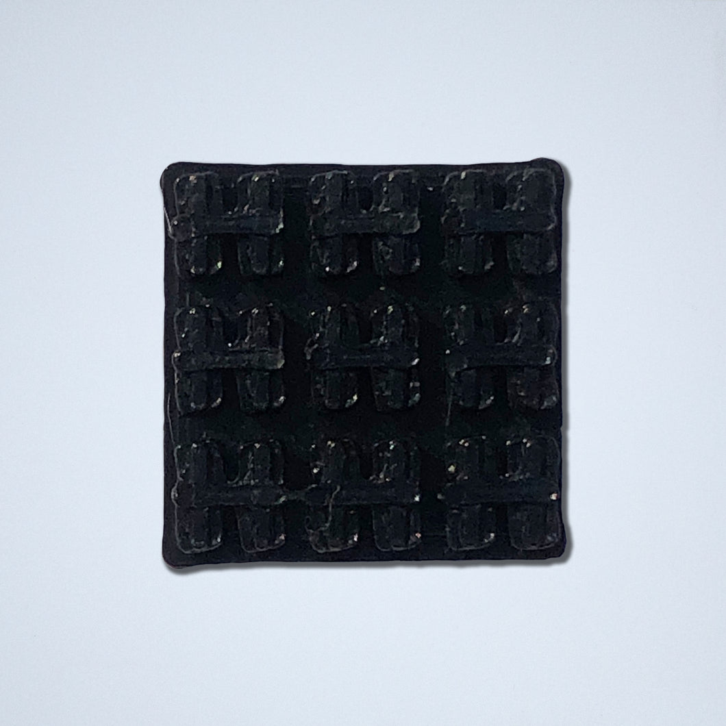 A half-inch by half-inch textured square sticker from Styklet featuring a black wafer pattern, shown in black.