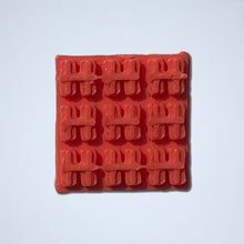 Load image into Gallery viewer, A half-inch by half-inch textured square sticker from Styklet featuring a black wafer pattern, shown in a red-orange coral color.