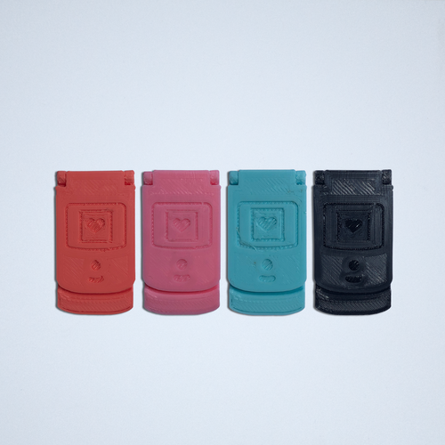 Four flip phone stickers from Styklet, in coral, pink, turquoise, and black, shown closed.