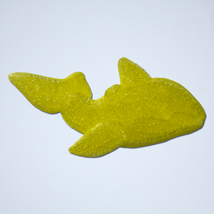 A 3D sticker of an orca whale floatie in translucent yellow.