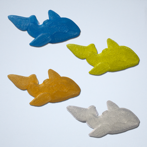 Four 3D stickers of whale floaties from Styklet in translucent blue, yellow, orange, and white.