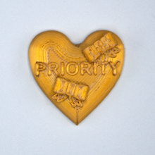 "Load image into Gallery viewer, Gold Candy Heart sticker from Styklet with the text ""Priority."""