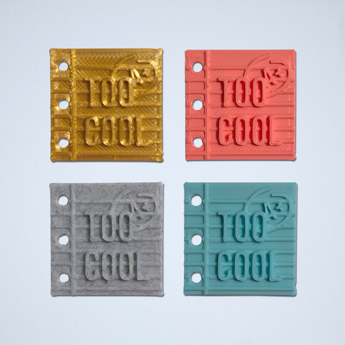 A set of four Too Cool stickers in gold, coral, gray and turquoise.