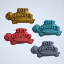 Load image into Gallery viewer, A set of four Try Harder 3D stickers in gold, turquoise, coral and gray.