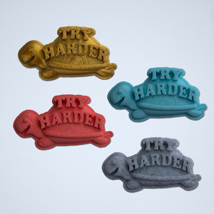 A set of four Try Harder 3D stickers in gold, turquoise, coral and gray.