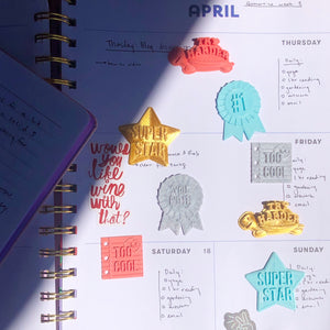 A set of You Win! 3D stickers adorning a daily planner, featuring two Try Harder Styklets in gold and coral.