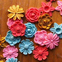 Load image into Gallery viewer, A bunch of colorful flower 3D stickers from Styklet on a wood background.