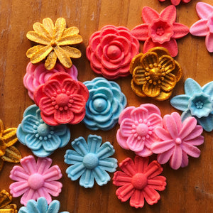 A bunch of colorful flower 3D stickers from Styklet on a wood background.