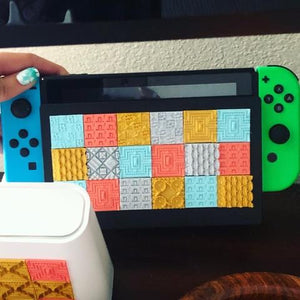 A series of Styklets from the Squares collection featuring a gold Victorian Blossom 3D sticker adorning a nintendo switch.