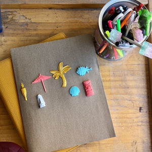 The Tiki Time 3D sticker kit adorning a notebook, featuring a gold palm tree, a gold tiki torch, a coral drink umbrella, a turquoise pufferfish, a turquoise clam, a gray tiki island head, and a coral tiki totem head.
