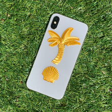 Load image into Gallery viewer, Gold palm tree and clamshell stickers from the Tiki Time collection adorning an iPhone .