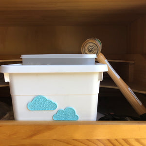 Two turquoise cloud 3D stickers on a white box.